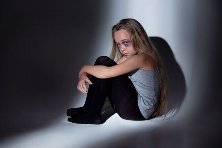 Sad and frightened little girl with bloodshot, bruised eyes sitting scared. Concept of child violence, domestic abuse. Sad, depressed being victim of parents and their agression. Childrens rights. 스톡 콘텐츠 - 133752485