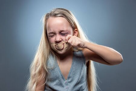Sad and frightened little girl with bloodshot, bruised eyes and false smile on her mouth. Concept of child violence, domestic abuse. Depressed being victim of parents. Illusion of happy childhood. 스톡 콘텐츠