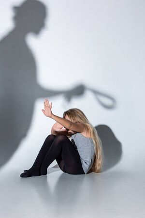 Sad and frightened little girl with bloodshot, bruised eyes crying scared of shadow on the wall. Concept of child violence, domestic abuse. Sad, depressed being victim of parents and their agression.