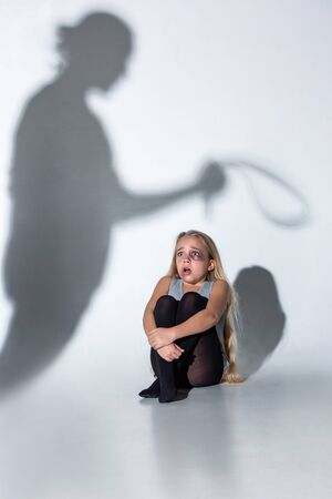 Sad and frightened little girl with bloodshot, bruised eyes crying scared of shadow on the wall. Concept of child violence, domestic abuse. Sad, depressed being victim of parents and their agression. 스톡 콘텐츠 - 133752526