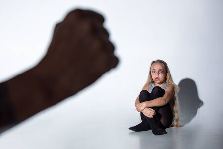 Sad and frightened little girl with bloodshot, bruised eyes crying scared of mans hand in front. Concept of child violence, domestic abuse. Sad, depressed being victim of parents and their agression.