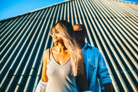 Tanned young caucasian couple, modern lovestory in film grain effect and vintage style. Sunset time. Walking on citys street, hauses roofs, summer evening. Honeymoon concept. Toned in teal orange. Zdjęcie Seryjne