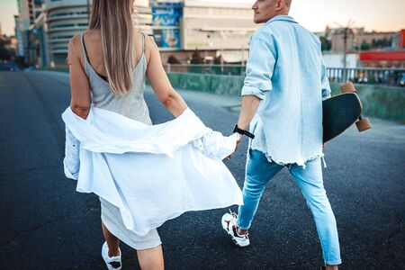Tanned young caucasian couple, modern lovestory in film grain effect and vintage style. Sunset time. Walking on the citys street, summer evening and sunlight. Honeymoon concept. Toned in teal orange.