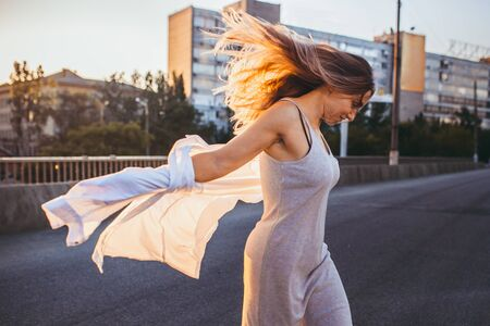 Young caucasian woman dancing and laughting, modern shot in film grain effect and vintage style. Sunset in summer evening. Citys street and roofs of houses. Toned in teal orange. Looks light.