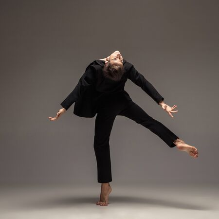 Man in casual office style clothes moving and dancing isolated on grey background. Art, motion, action, flexibility, inspiration concept. Flexible caucasian ballet dancer, weightless movement. 版權商用圖片