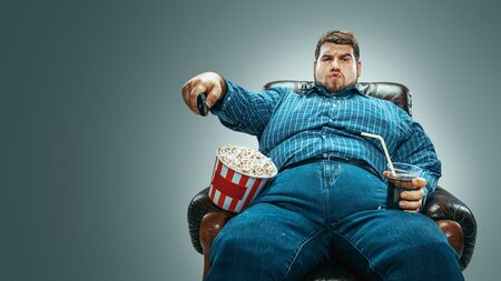 Portrait of fat caucasian man wearing jeanse and whirt sitting in a brown armchair on gradient grey background. Watching TV drinks cola, eats popcorn and changing channels. Overweight, carefree. Banco de Imagens