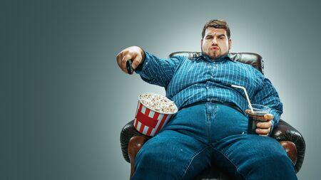 Ritratto di uomo caucasico grasso che indossa jeans e whirt seduto in una poltrona marrone su sfondo grigio sfumato. Guardare la TV beve cola, mangia popcorn e cambia canale. Sovrappeso, spensierato.