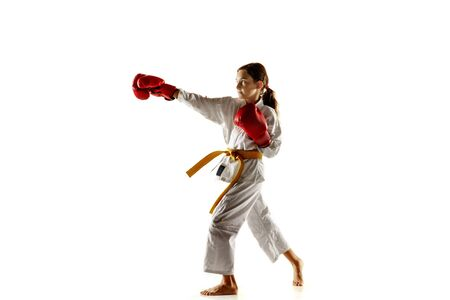 Confident junior in kimono practicing hand-to-hand combat, martial arts. Young female fighter with yellow belt s training on white studio background. Concept of healthy lifestyle, sport, action. Stock Photo
