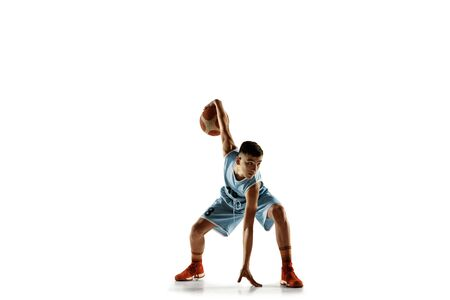 Full length portrait of young basketball player with a ball isolated on white studio background. Teenager training and practicing in action, motion. Concept of sport, movement, healthy lifestyle, ad. Stock Photo