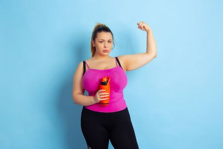 Young caucasian plus size female models training on blue background. Concept of sport, human emotions, expression, healthy lifestyle, body positive, equality. Posing with bottle, copyspace.
