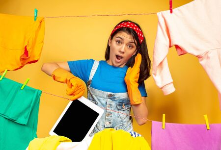 Funny and beautiful housewife doing housework isolated on yellow background. Young caucasian woman surrounded by washed clothes. Domestic life, bright artwork, housekeeping concept. Has washed tablet. Stok Fotoğraf