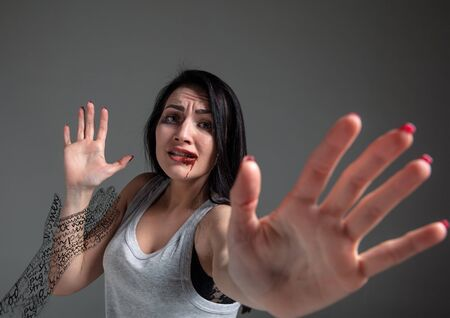 Woman in fear of domestic abuse, violence, concept of female rights. Brunette woman on grey background looks sad, depressed being victim of man or husband. Has bruises, hematomas. Invisible male hand. 스톡 콘텐츠