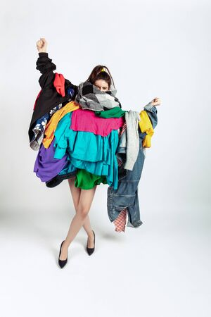Woman addicted of sales, clothes, overproduction and crazy demand. Female model wearing too much colorful clothes, need more things to be happy. Fashion, style, black friday, sale, abusing purchases.