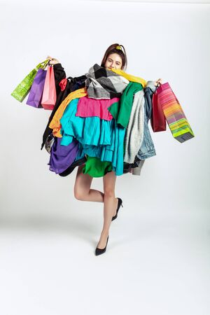 Shopping like an issue. Woman addicted of sales. Overproduction and crazy demand. Female model wearing too much colorful clothes, need more. Fashion, style, black friday, sale, abusing purchases. Stockfoto