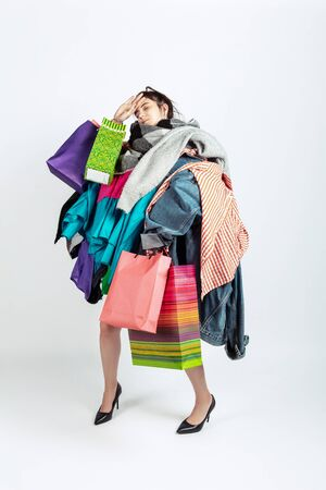 Shopping like an issue. Woman addicted of sales. Overproduction and crazy demand. Female model wearing too much colorful clothes, need more. Fashion, style, black friday, sale, abusing purchases.