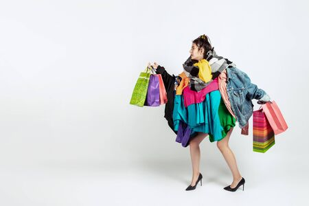 Shopping like an issue. Woman addicted of sales. Overproduction and crazy demand. Female model wearing too much colorful clothes, need more. Fashion, style, black friday, sale, abusing purchases. Reklamní fotografie