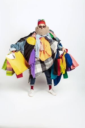 Shopping like an issue. Man addicted of sales. Overproduction and crazy demand. Female model wearing too much colorful clothes, need more. Fashion, style, black friday, sale, abusing purchases. Stockfoto