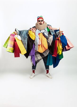 Shopping like an issue. Man addicted of sales. Overproduction and crazy demand. Female model wearing too much colorful clothes, need more. Fashion, style, black friday, sale, abusing purchases.