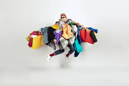 Shopping like an issue. Man addicted of sales. Overproduction and crazy demand. Female model wearing too much colorful clothes, need more. Fashion, style, black friday, sale, abusing purchases. Jumping. Reklamní fotografie