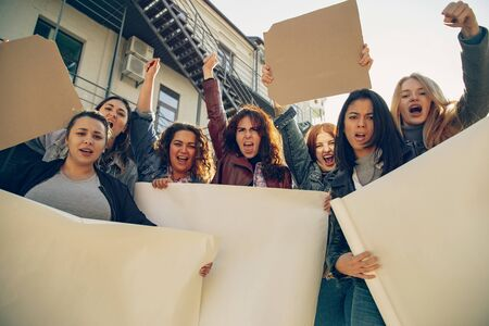 Young people protesting of womens rights and equality on the street. Caucasian women have meeting about problem in workplace, male pressure, domestic abuse, harassment. Copyspace. Holding posters. Archivio Fotografico - 134395510