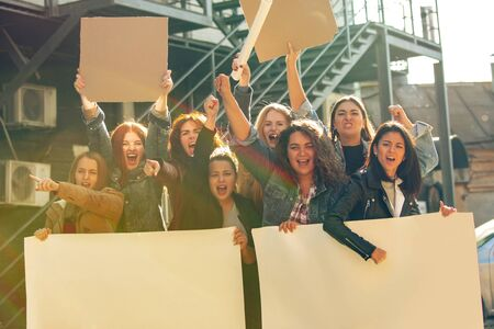 Young people protesting of womens rights and equality on the street. Caucasian women have meeting about problem in workplace, male pressure, domestic abuse, harassment. Copyspace. Holding posters. Archivio Fotografico - 134395564