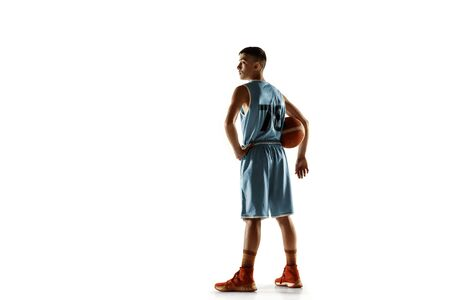 Full length portrait of young basketball player with a ball isolated on white studio background. Teenager confident posing with ball. Concept of sport, movement, healthy lifestyle, ad, action, motion. Stock Photo