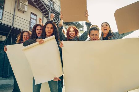 Young people protesting of womens rights and equality on the street. Caucasian women have meeting about problem in workplace, male pressure, domestic abuse, harassment. Copyspace. Holding posters. Archivio Fotografico - 134404737