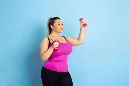 Young caucasian plus size female models training on blue background. Concept of sport, human emotions, expression, healthy lifestyle, body positive, equality. Training with the weights, copyspace.