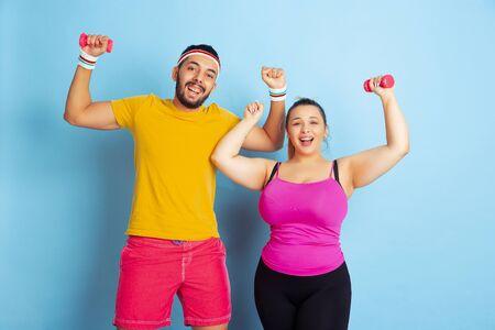 Junges hübsches kaukasisches Paar in heller Kleidung, die auf blauem Hintergrund trainiert Konzept des Sports, der menschlichen Emotionen, des Ausdrucks, des gesunden Lebensstils, der Beziehung, der Familie. Training mit Gewichten, viel Spaß.