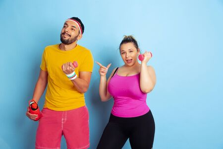 Young pretty caucasian couple in bright clothes training on blue background Concept of sport, human emotions, expression, healthy lifestyle, relation, family. Training with weights, have fun.