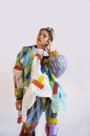 Woman wearing plastic on white background. Female model in clothes and shoes made of garbage. Fashion, style, recycling, eco and environmental concept. Too much pollution, were eating and taking it. Imagens - 134459038