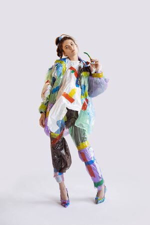Woman wearing plastic on white background. Female model in clothes and shoes made of garbage. Fashion, style, recycling, eco and environmental concept. Too much pollution, were eating and taking it.