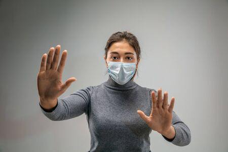 Stop it.. Caucasian woman wearing the respiratory protection mask against air pollution and dust particles exceed the safety limits. Healthcare, environmental, ecology concept. Allergy, headache. Stok Fotoğraf