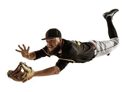 Im Flug. Baseballspieler, Krug in schwarzer Uniform, die auf weißem Hintergrund übt und trainiert. Junger Berufssportler in Aktion und Bewegung. Gesunder Lebensstil, Sport, Bewegungskonzept.