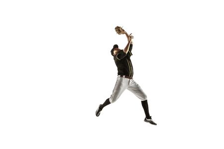In jump. Baseball player, pitcher in black uniform practicing and training isolated on white background. Young professional sportsman in action and motion. Healthy lifestyle, sport, movement concept.