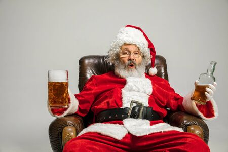 Santa Claus drinking beer sitting on armchair, congratulating, looks drunk and happy. Caucasian male model in traditional costume. New Year 2020, gifts, holidays, winter mood. Copyspace for your ad.