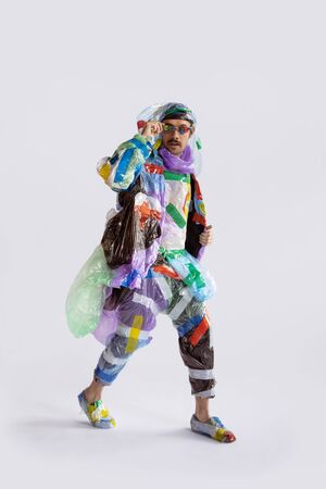 Man wearing plastic on white background. Male model in clothes made of garbage. Fashion, style, recycling, eco and environmental concept. Too much pollution, were eating and taking it. Waste products.
