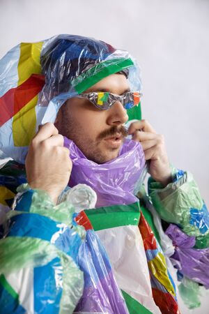 Close up of man wearing plastic on white background. Male model in clothes made of garbage. Fashion, style, recycling, eco and environmental concept. Too much pollution, were eating and taking it.