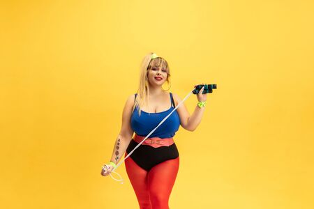 Young caucasian plus size female models training on yellow background. Stylish woman in bright clothes. Copyspace. Concept of sport, healthy lifestyle, body positive, fashion. Posing with jump rope.