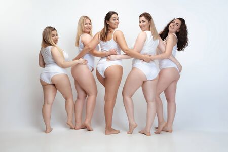 In love with myself. Portrait of beautiful plus size young women posing on white background. Happy smiling female models hugging. Concept of body positive, beauty, fashion, style, feminism. Фото со стока