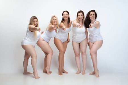 In love with myself. Portrait of beautiful plus size young women posing on white background. Happy smiling female models pointing on. Concept of body positive, beauty, fashion, style, feminism.