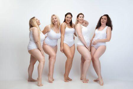 Enamorado de mi mismo. Retrato de hermosas mujeres jóvenes de talla grande posando sobre fondo blanco. Modelos femeninos sonrientes felices riendo juntos. Concepto de cuerpo positivo, belleza, moda, estilo, feminismo.