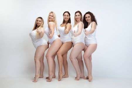 In love with myself. Portrait of beautiful plus size young women posing on white background. Happy smiling female models with thumb up. Concept of body positive, beauty, fashion, style, feminism.