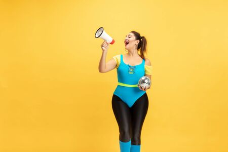Young caucasian plus size female models training on yellow background. Stylish woman in bright clothes. Copyspace. Concept of sport, healthy lifestyle, body positive, fashion. Calling with discoball.