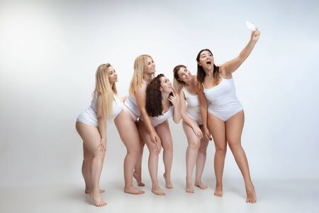 In love with myself. Portrait of beautiful plus size young women posing on white background. Happy smiling female models making selfie. Concept of body positive, beauty, fashion, style, feminism.