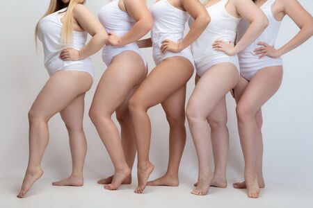 In love and harmony with myself. Close up of plus size young women posing on white background. Female models in white swimsuit. Concept of body positive, beauty, fashion, style, feminism. Zdjęcie Seryjne
