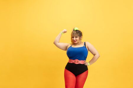 Young caucasian plus size female models training on yellow background. Stylish woman in bright clothes. Copyspace. Concept of sport, healthy lifestyle, body positive, fashion. Girl power and strenght. Stock Photo