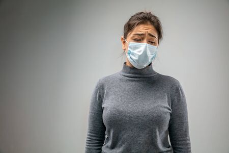 Cant breathe. Caucasian woman wearing the respiratory protection mask against air pollution and dust particles exceed the safety limits. Healthcare, environmental, ecology concept. Allergy, headache.