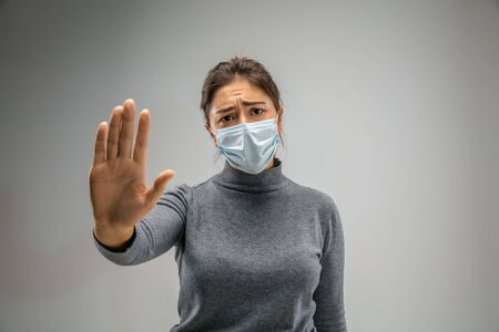 Stop it.. Caucasian woman wearing the respiratory protection mask against air pollution and dust particles exceed the safety limits. Healthcare, environmental, ecology concept. Allergy, headache. Imagens