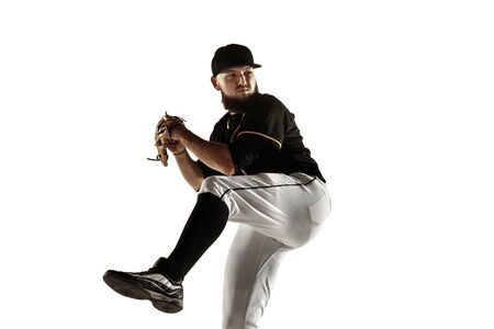 Baseball player, pitcher in a black uniform practicing and training isolated on a white background. Young professional sportsman in action and motion. Healthy lifestyle, sport, movement concept.